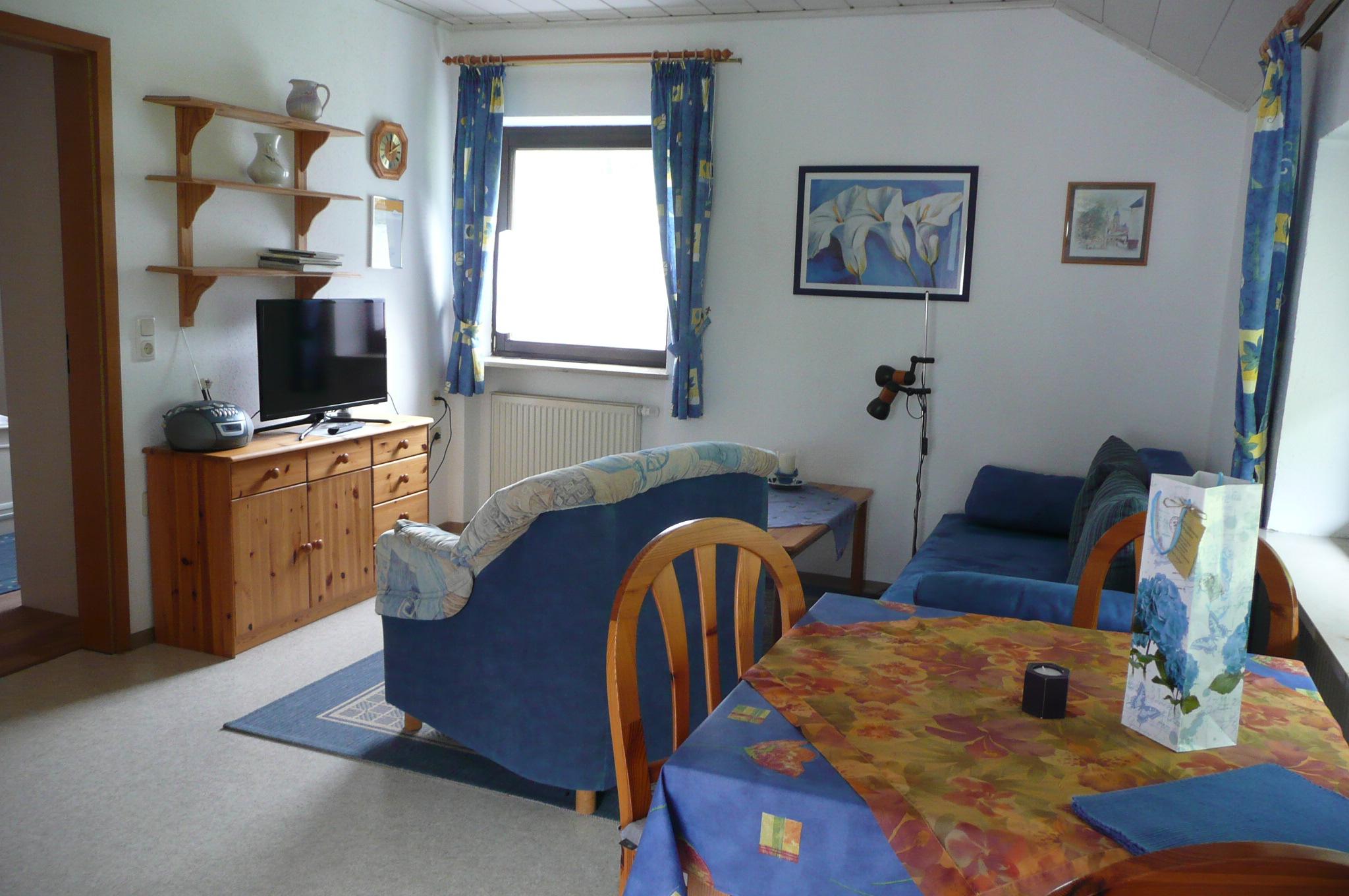 Wohnzimmer mit Holzmöbeln, Fernseher und blauen Sofas