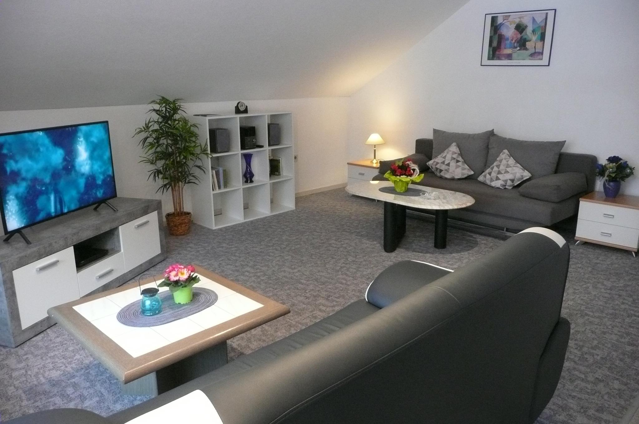 Wohnzimmer mit Dachschräge, Fernseher und zwei grauen Sofas