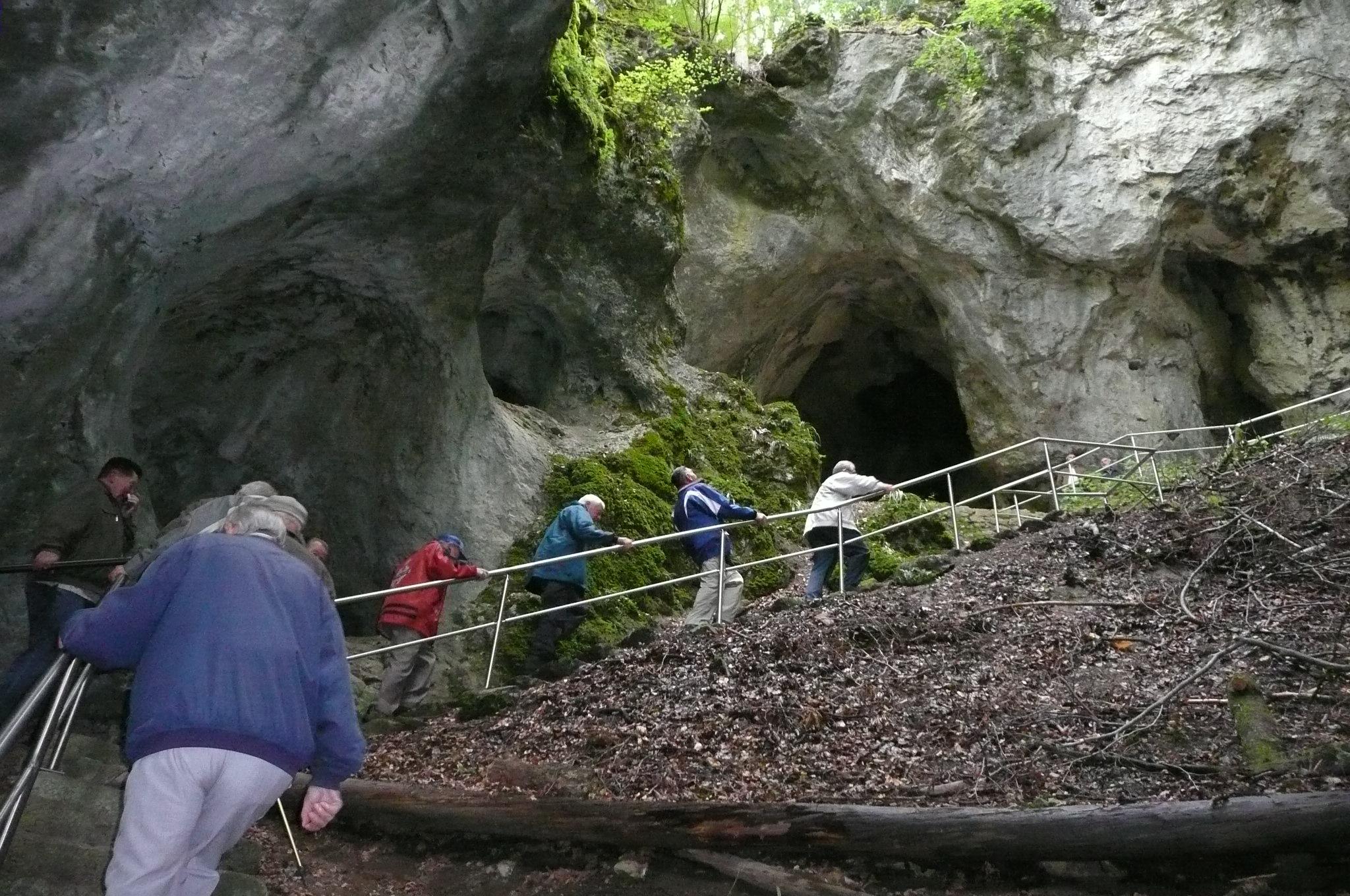 Wanderer steigen die Treppe in der eingestürzten Höhlenruine empor